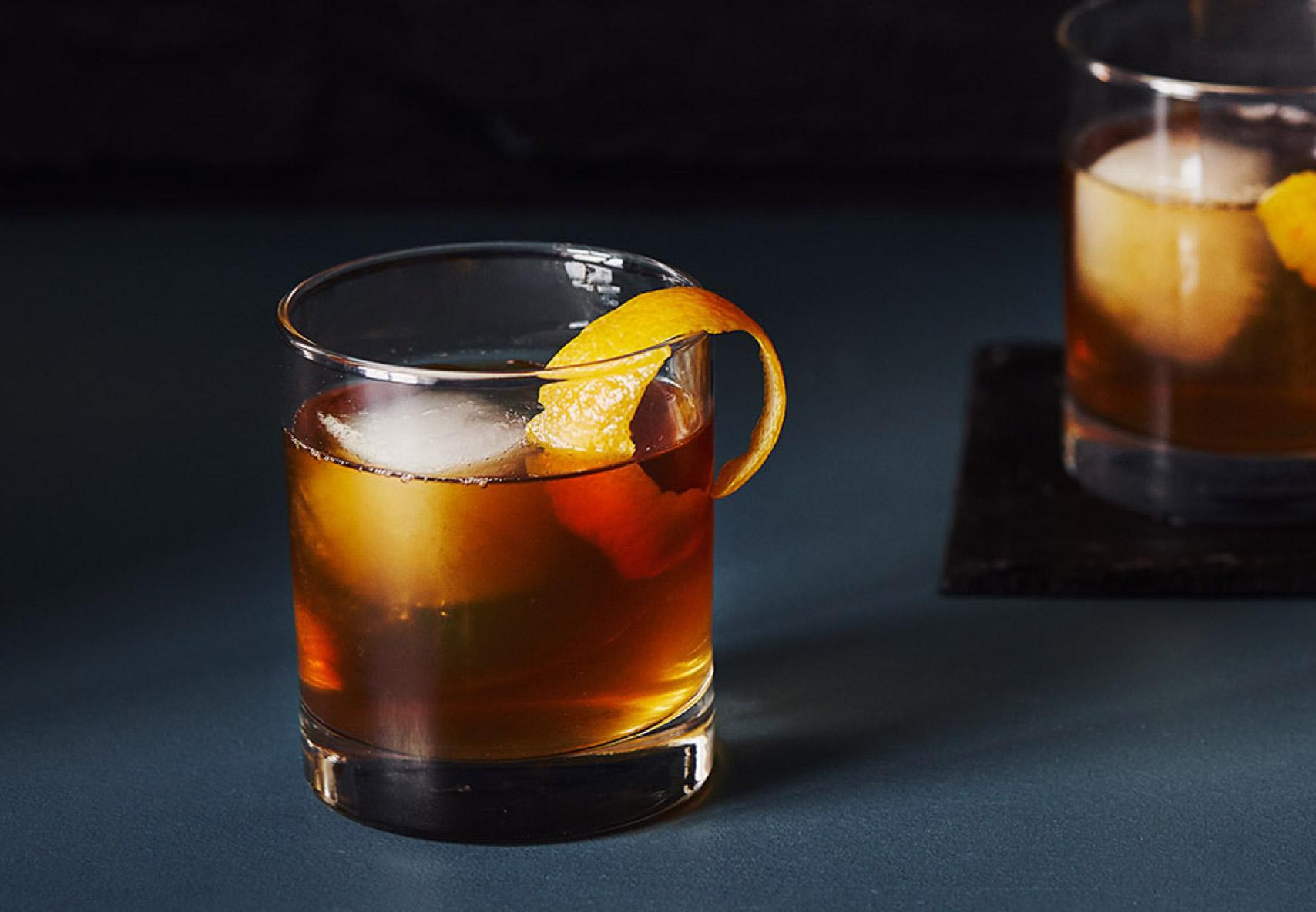 Deux verres à whisky remplis d'un délicieux mélange de bourbon, thé chai, amers, sirop d'érable et glace, surmontés d'une peau d'orange bouclée.