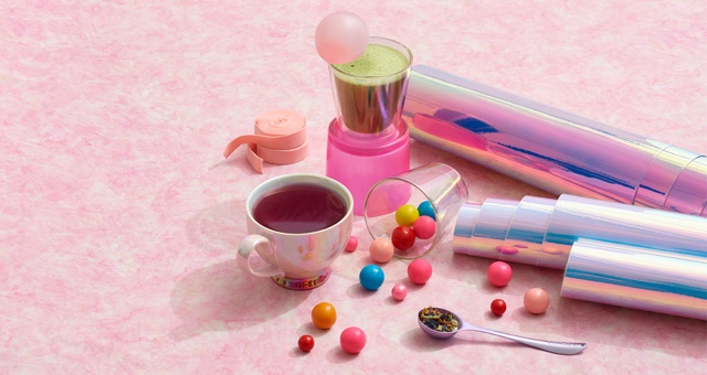 Ceramic teacup filled with tea, glass cup filled with matcha, loose leaf tea in spoon, bubble gum tape, colourful gum balls.