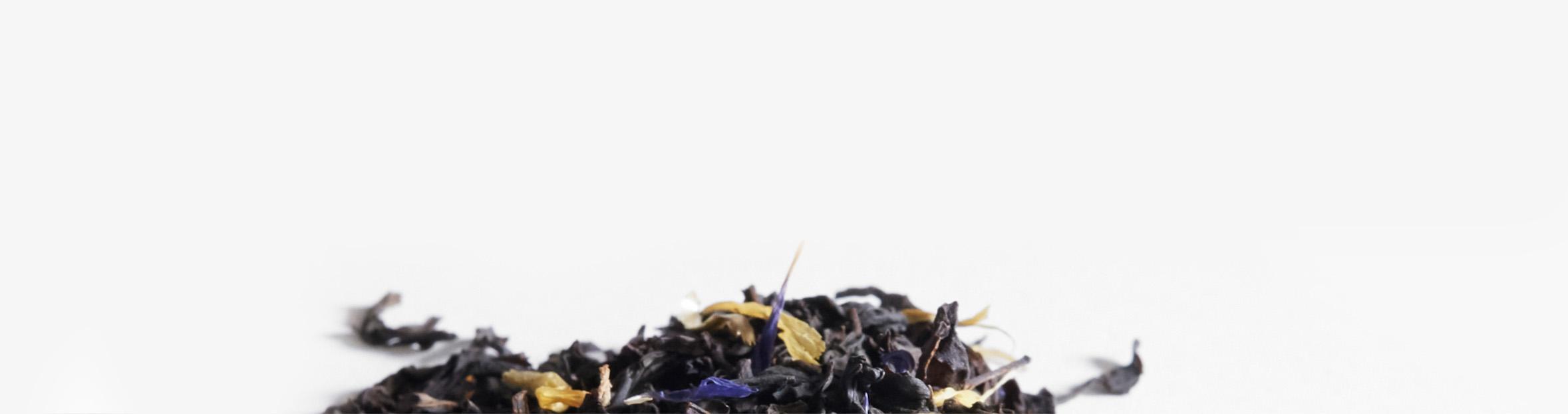 Les ingrédients crus d'Earl Grey crème biologique étalés sur un sol blanc : thé noir biologique, centaurées bleuets et soucis biologiques.