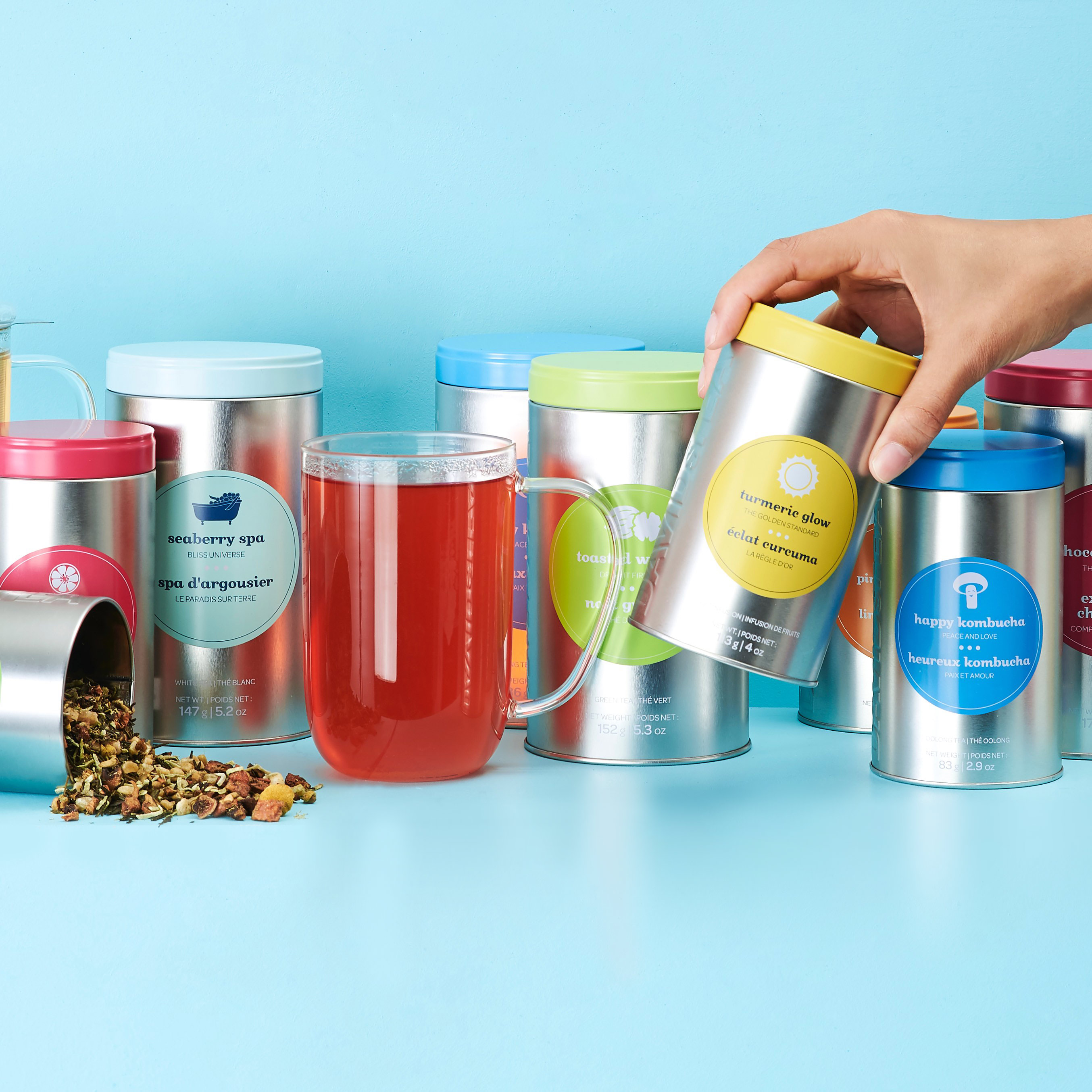 Various colourful tins with glass mug filled with tea.