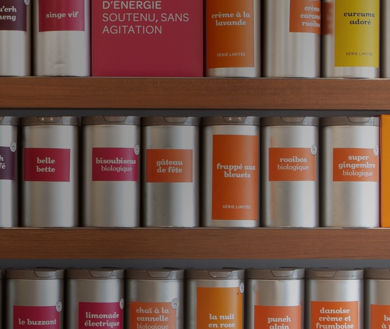 Tins of teas in a row on wooden shelves.