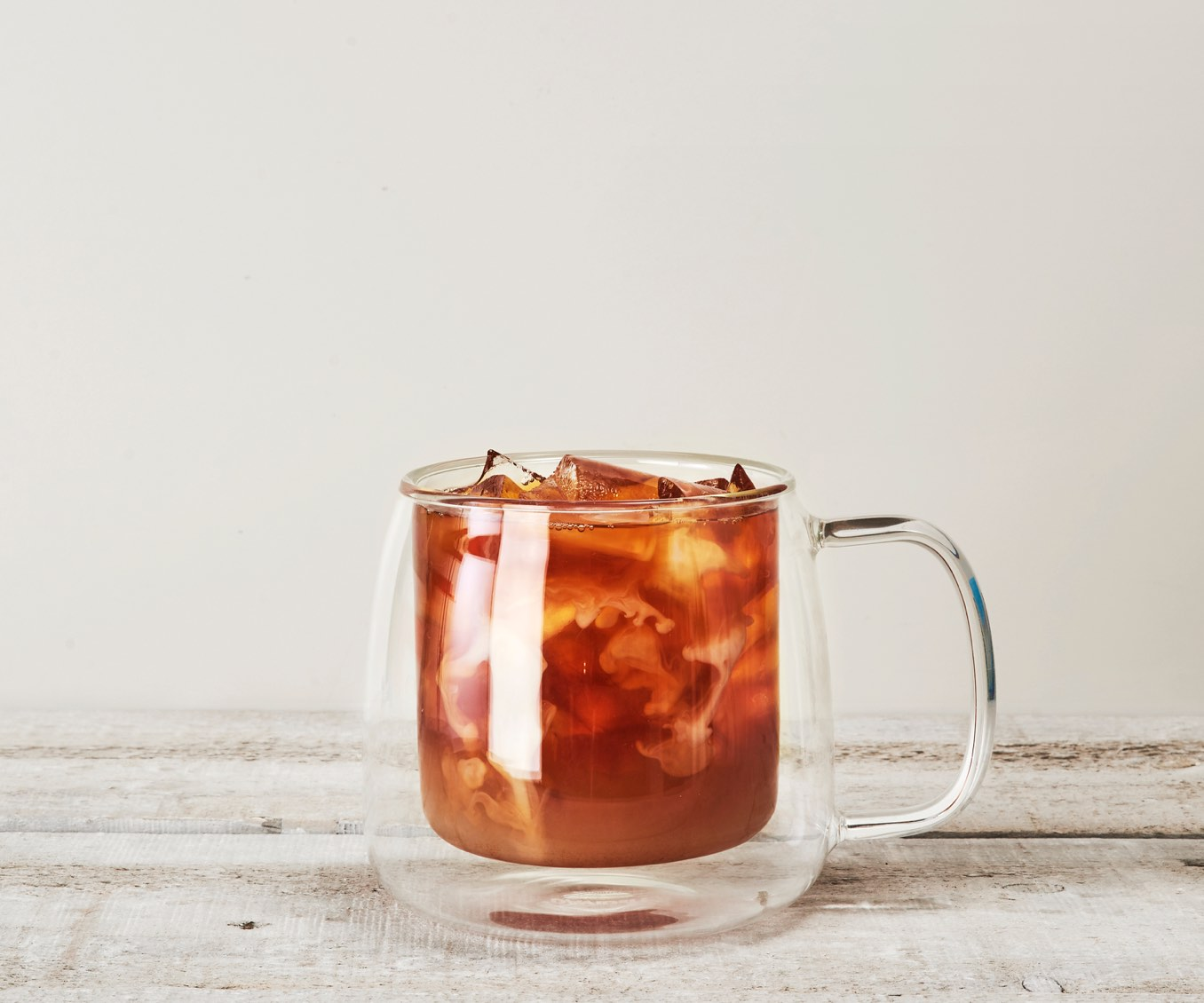 Clear 18 oz double walled glass latte mug filled with chai iced tea.