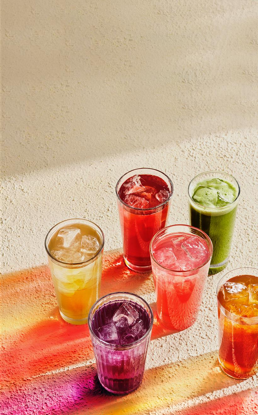 7 thés glacés infusés dans des verres transparents représentant un arc-en-ciel par leurs couleurs différentes.