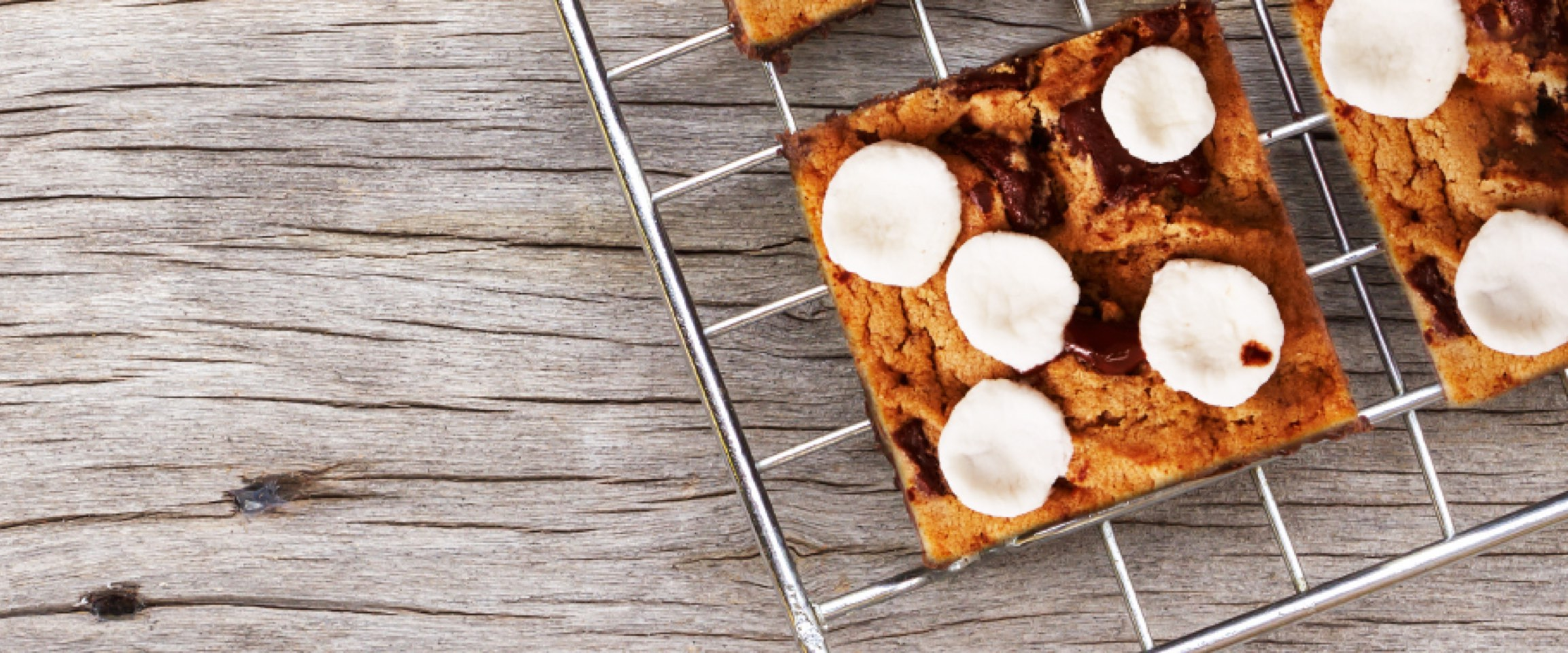 S'mores blondie squares topped with marshmallows on cooling rack.