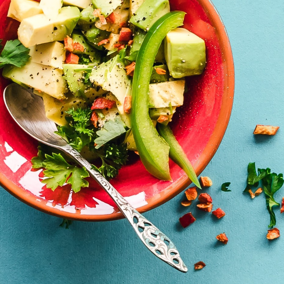 Bowl filled with a Greek salad – lettuce, sliced avocado, tomatoes, and seasoning.