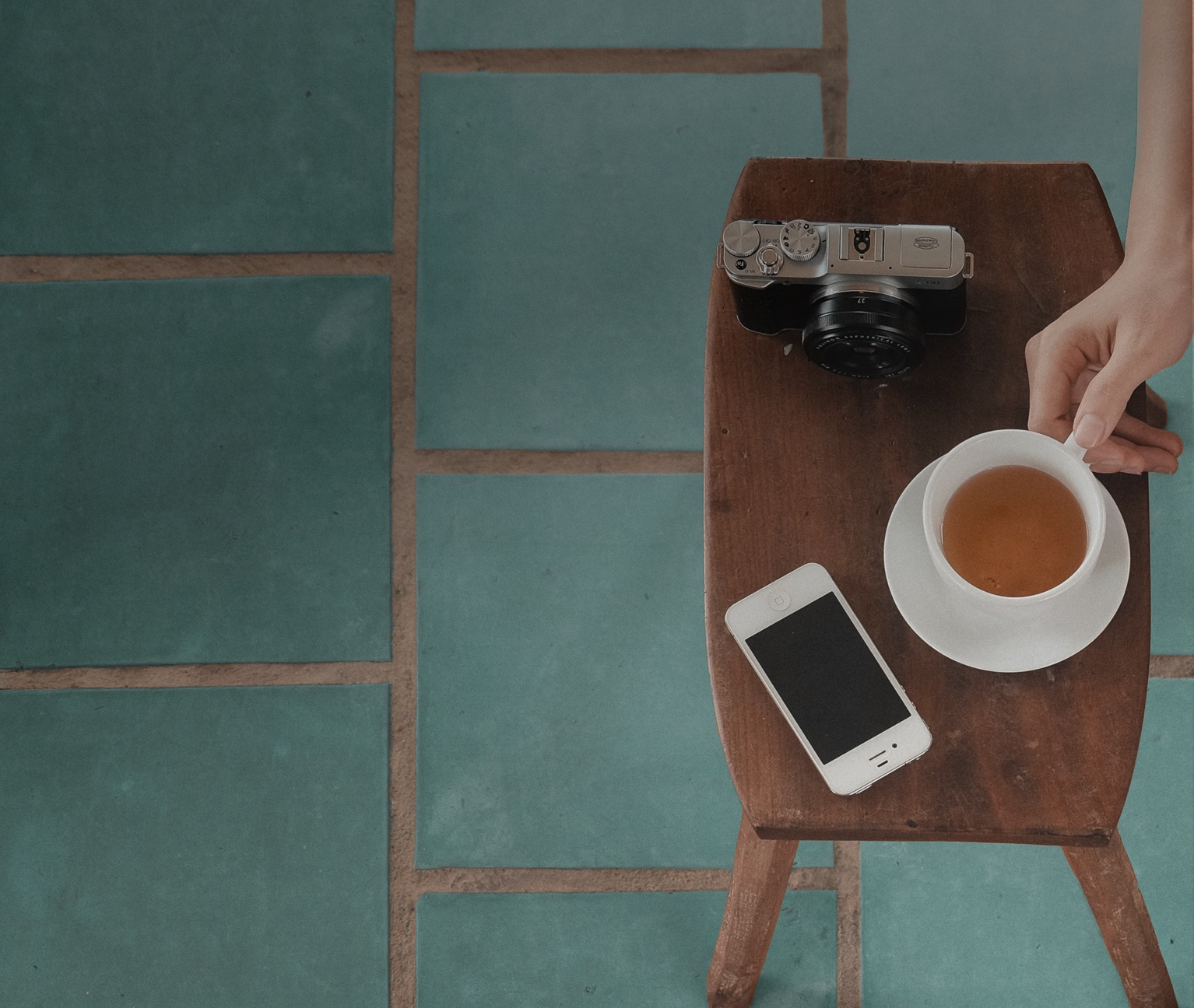 A shot from above of a white iPhone, tea cup and black camera on a wooden table and turquoise tiling.
