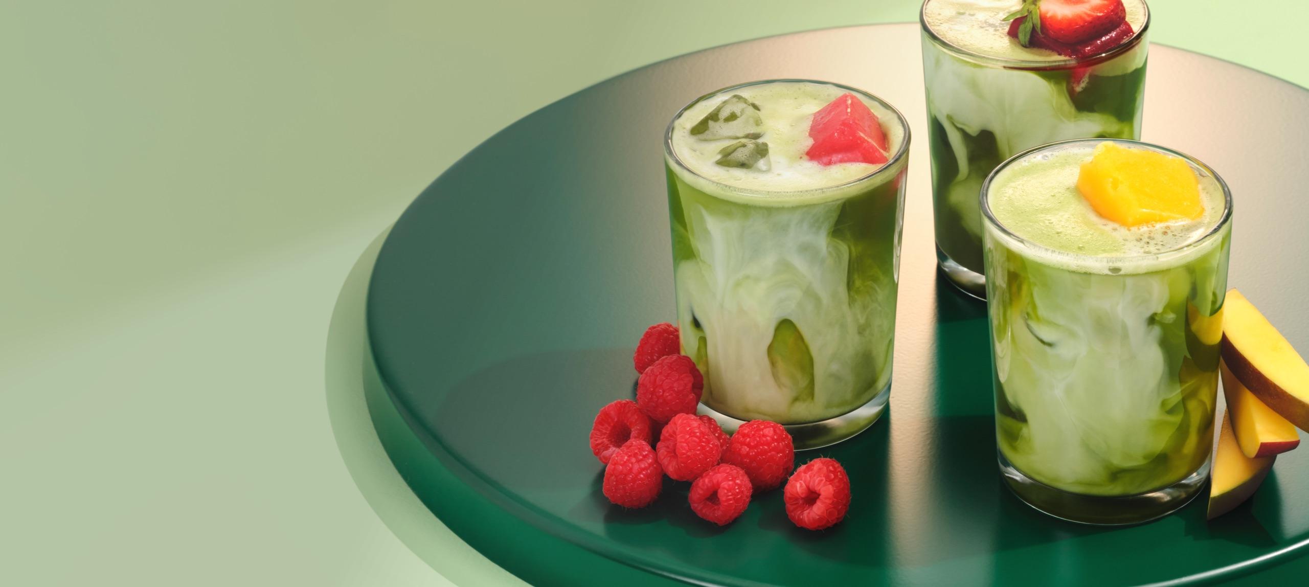 Trois verres remplis de matcha placés sur un cabaret circulaire avec des framboises, mangues et fraises sur le dessus.