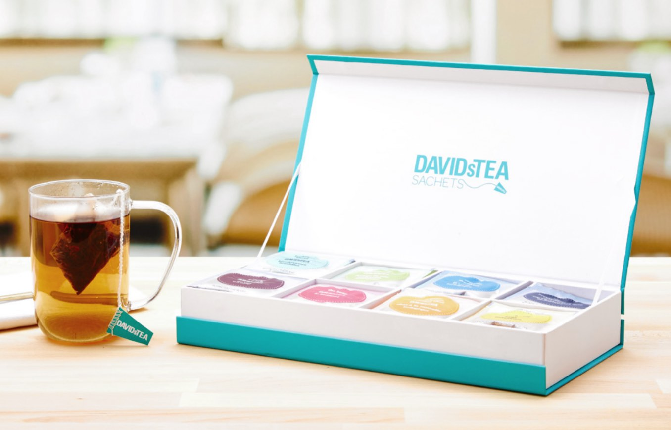 Teal cardboard sachet tea chest open on table with eight types of teas in sachets. Teabag in clear 16 oz glass mug with tea.