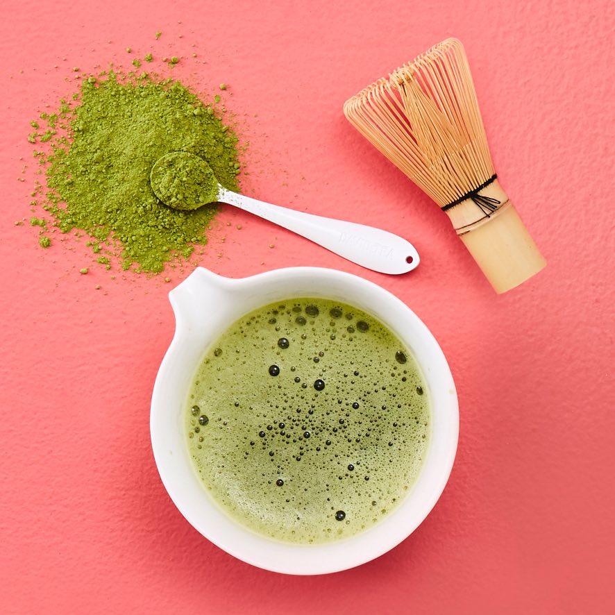 White ceramic matcha bowl with frothed matcha, spoon with green tea powder, traditional bamboo matcha whisk.