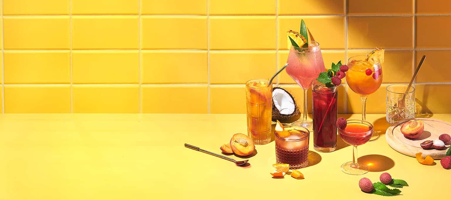 Des verres de différentes grosseurs remplis de thés glacés, entourés de fruits et d'accessoires.