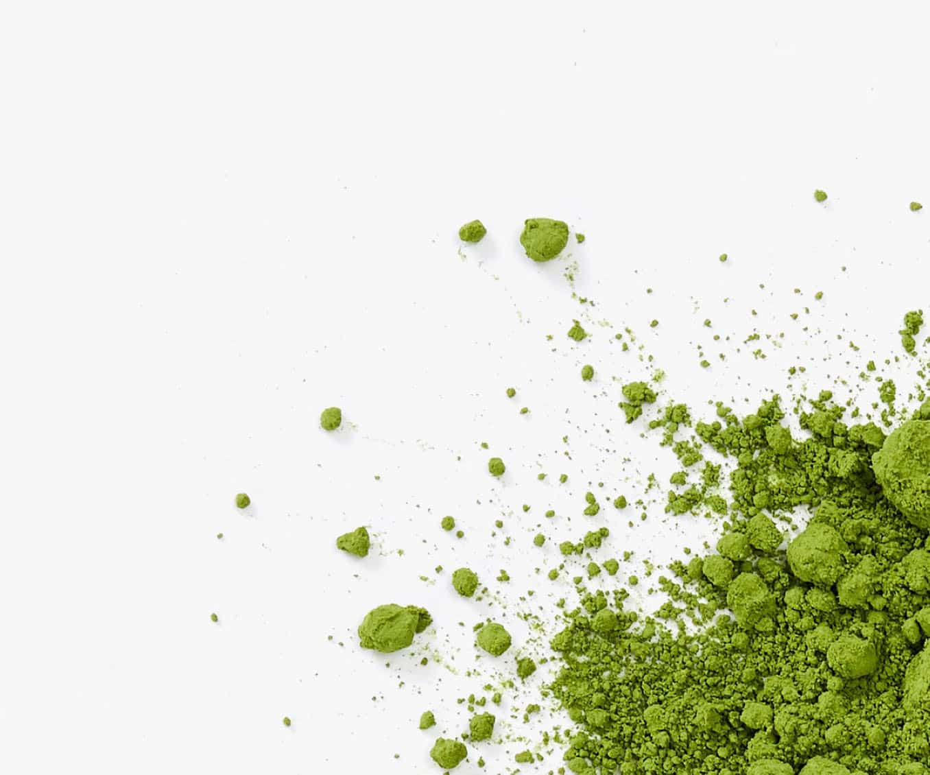 Loose leaf matcha powder placed in the bottom right corner on a white background.