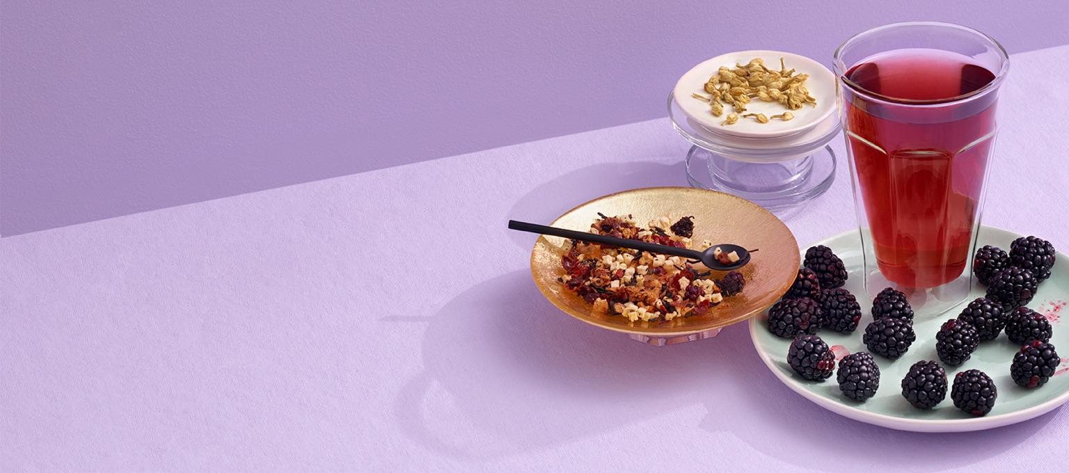 Grand verre transparent rempli de thé aux mûres sur une assiette de céramique avec mûres. Bol de thé en feuilles avec cuillère.