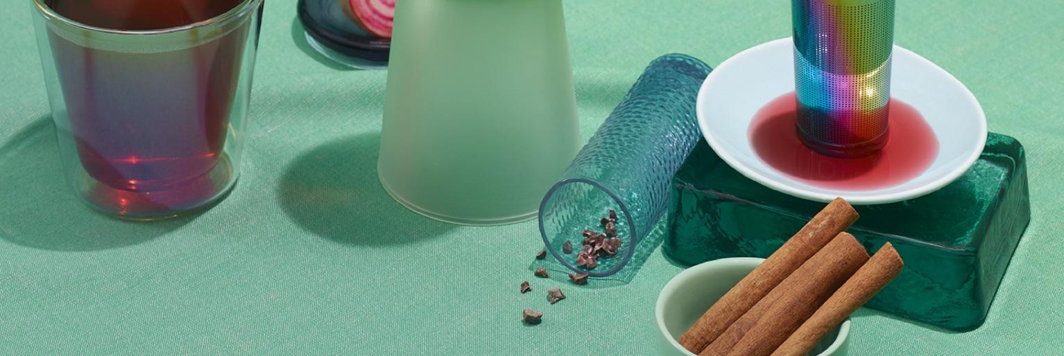 Des tasses variées remplies de thés sur une surface turquoise et entourées de bâtons de cannelle et d'un infuseur arc-en-ciel.