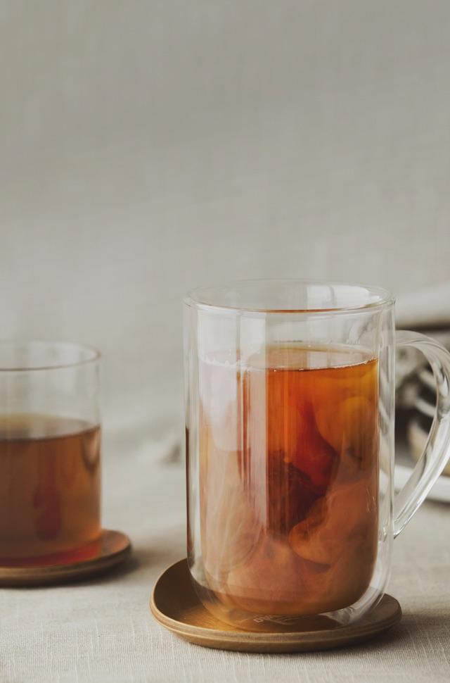 3 tasses en verre contenant divers thés, entourées de raisins verts et de tranches d'orange sur une plateau blanc.