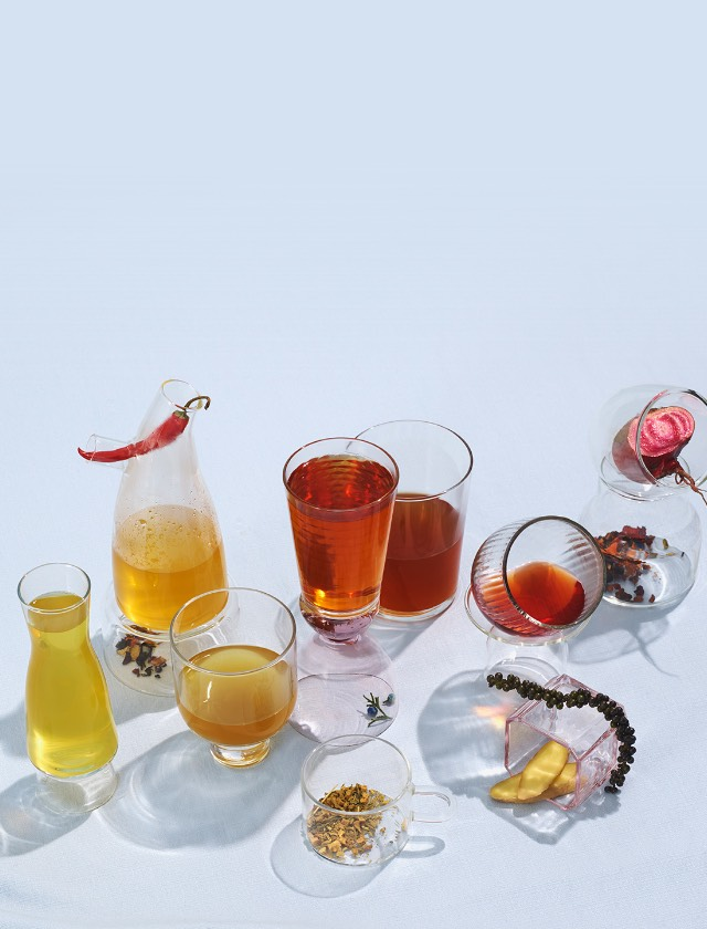 Various glasses filled with detox teas surrounded by various raw ingredients such as beets and peppers.