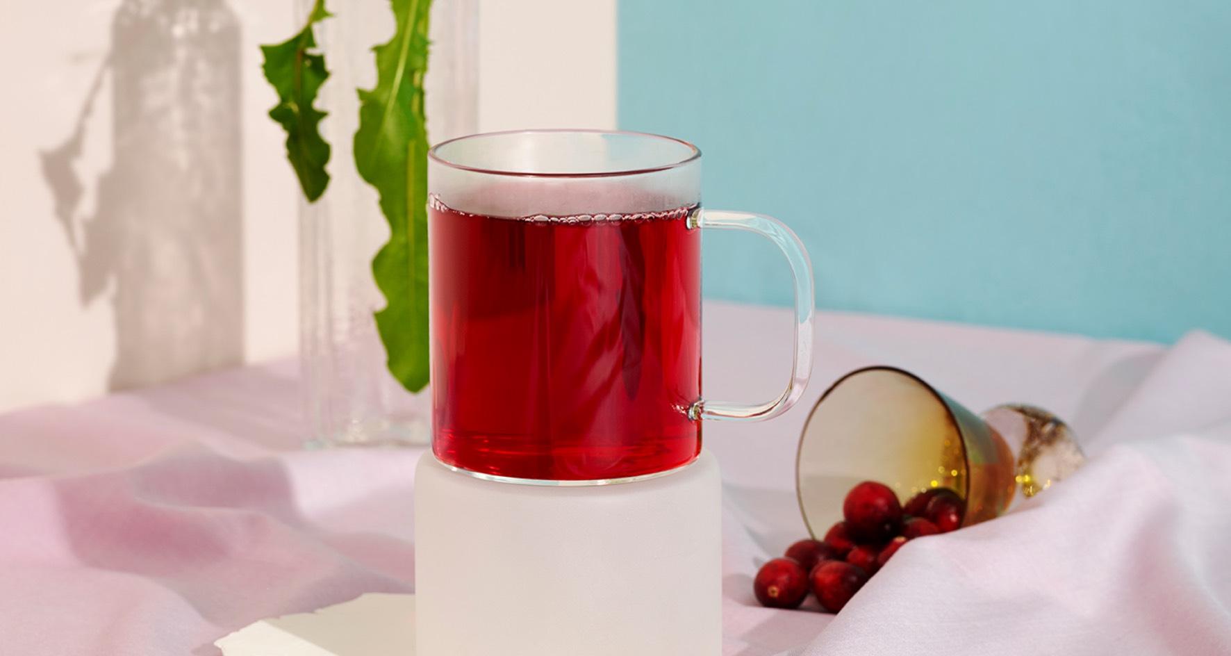 Une tasse transparente remplie de thé Détox aux canneberges.