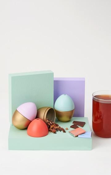 Trois boîtes en forme d'oeuf de Pâques avec thés en feuilles. Tasse 16 oz en verre remplie de thé.