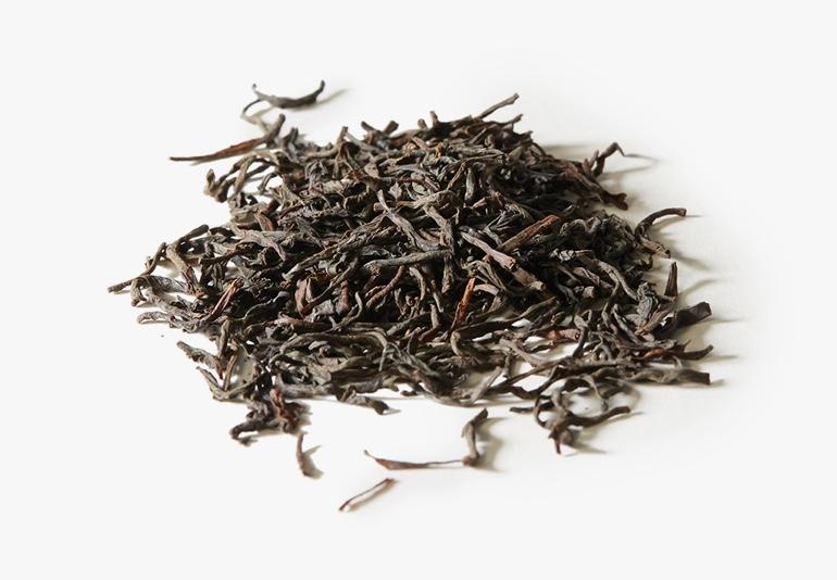 Des ingrédients du thé Orange Pekoe, placés sur une surface blanche.