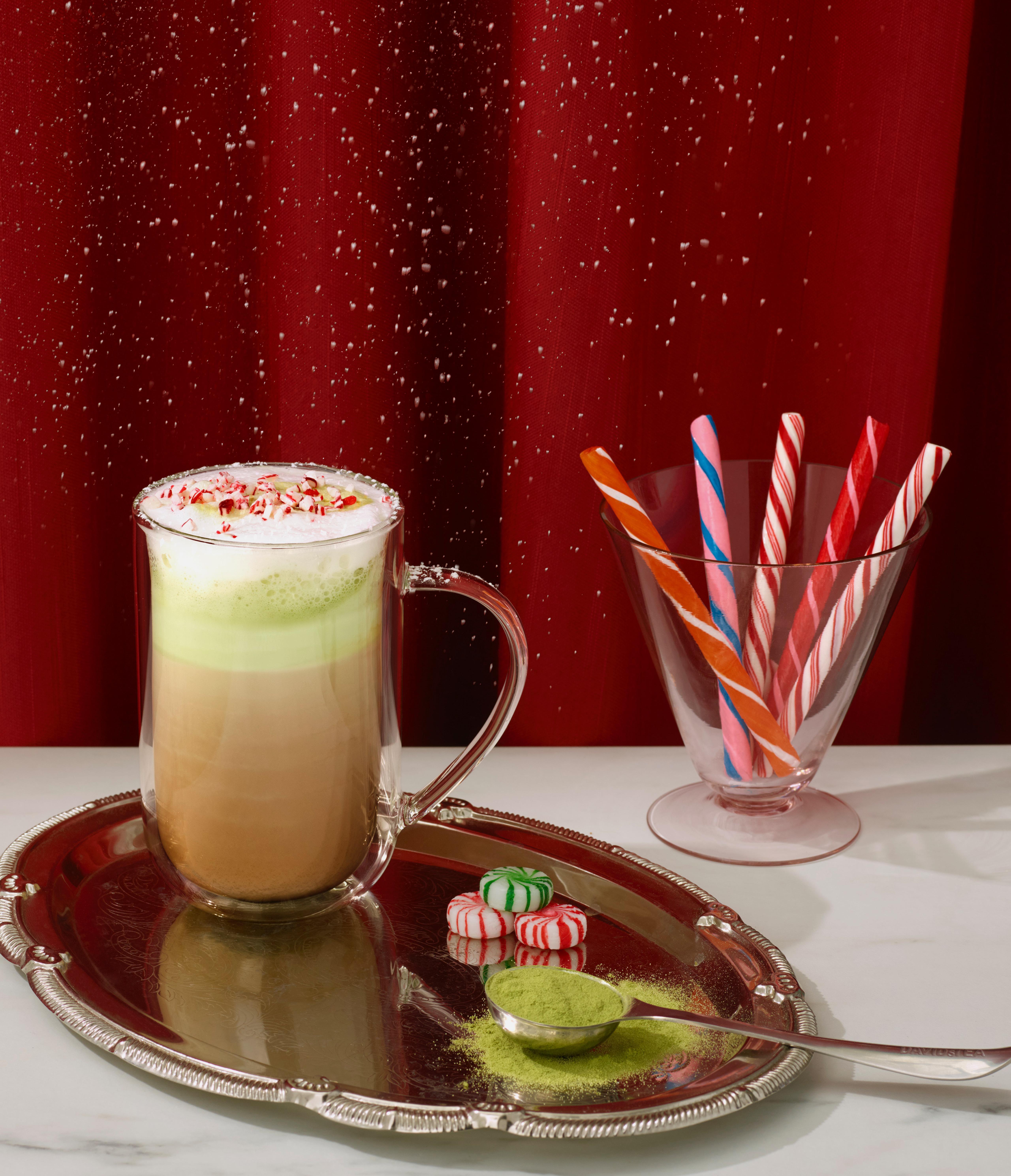 Une tasse remplie de Canne Craquante avec un shooter de matcha placée à côté d'une tasse transparente contenant 5 cannes colorés, trois bonbons et une Cuillère Parfaite.