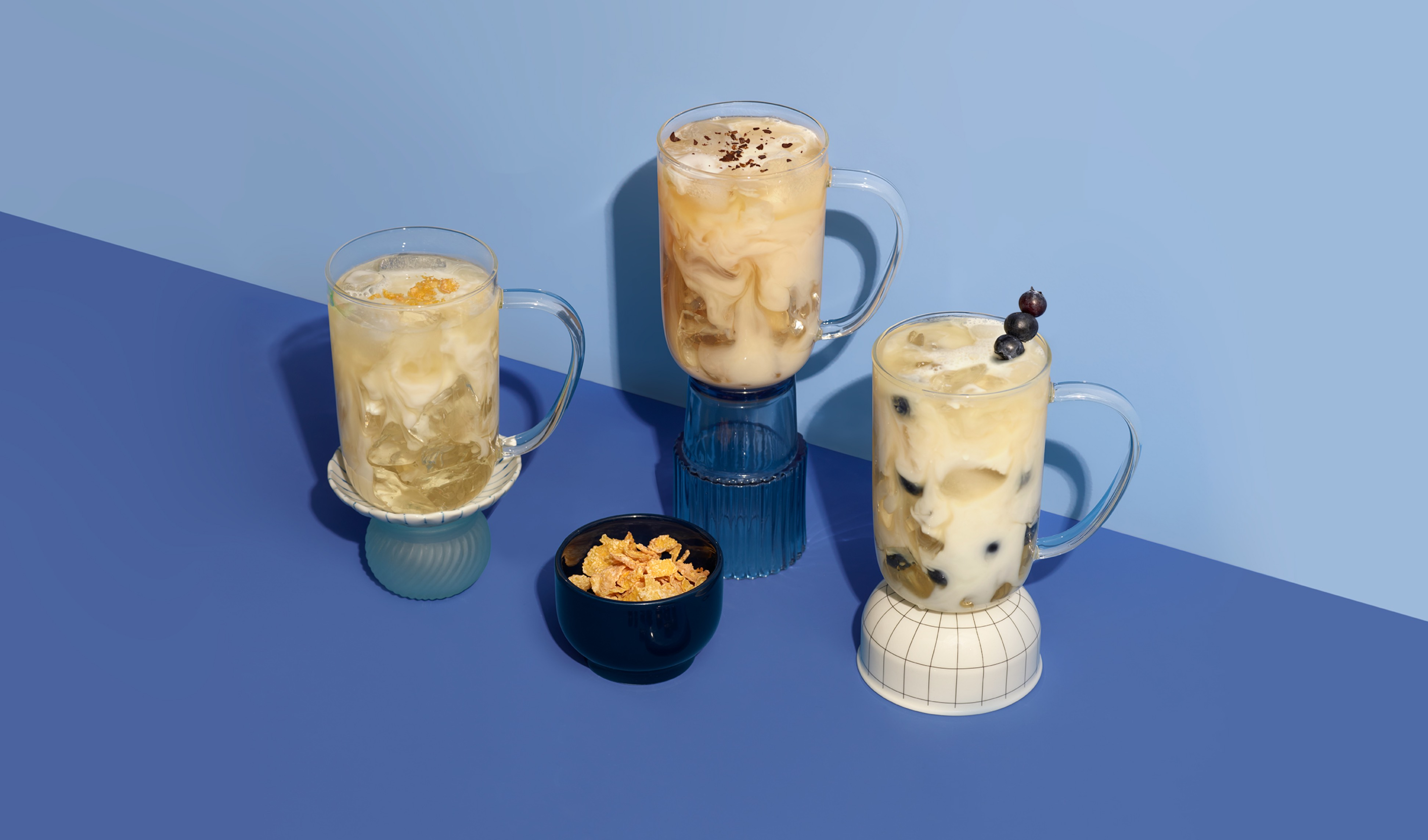 Three 16 oz clear cups with Frosted Cereal, Blueberry Shake and Vanilla Cappuccino iced lattes.