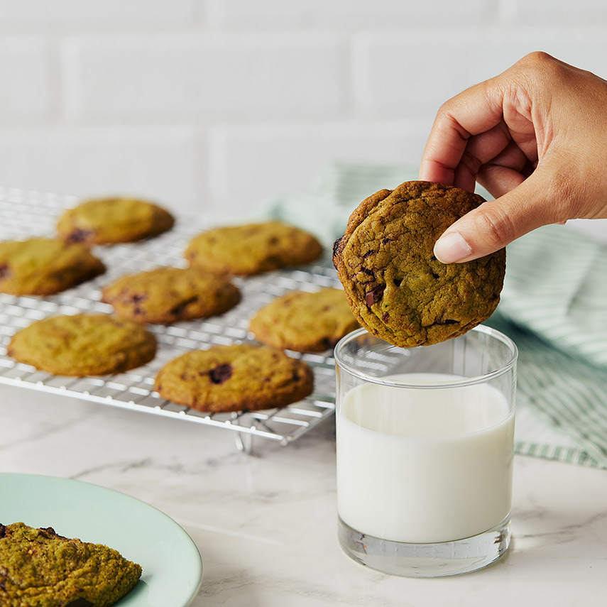 A hand is about to dip a chocolate chunk cookie into a small glass of milk, more cookies pictured in the background on a cooling rack.