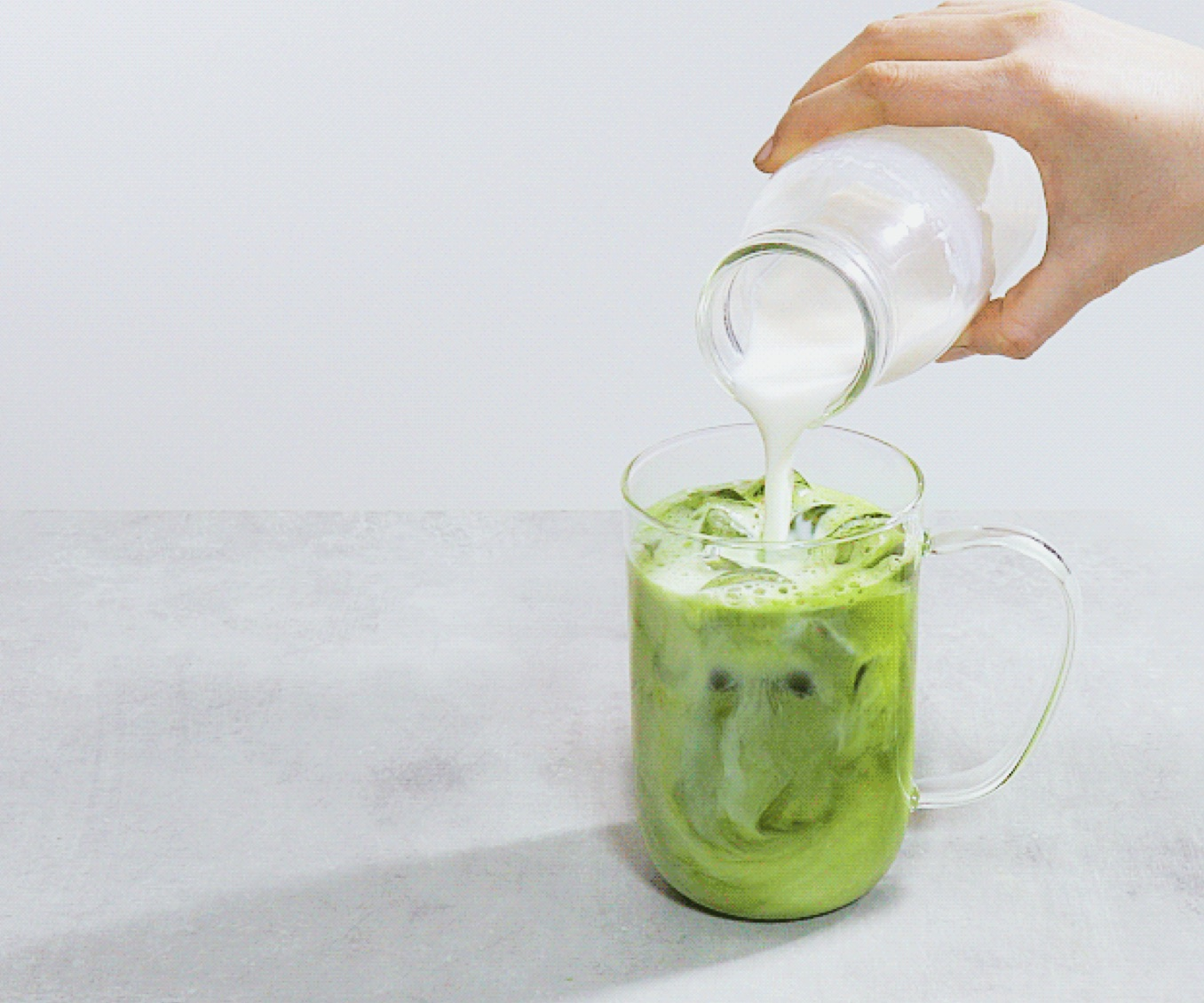 A Nordic mug filled with iced matcha latte.