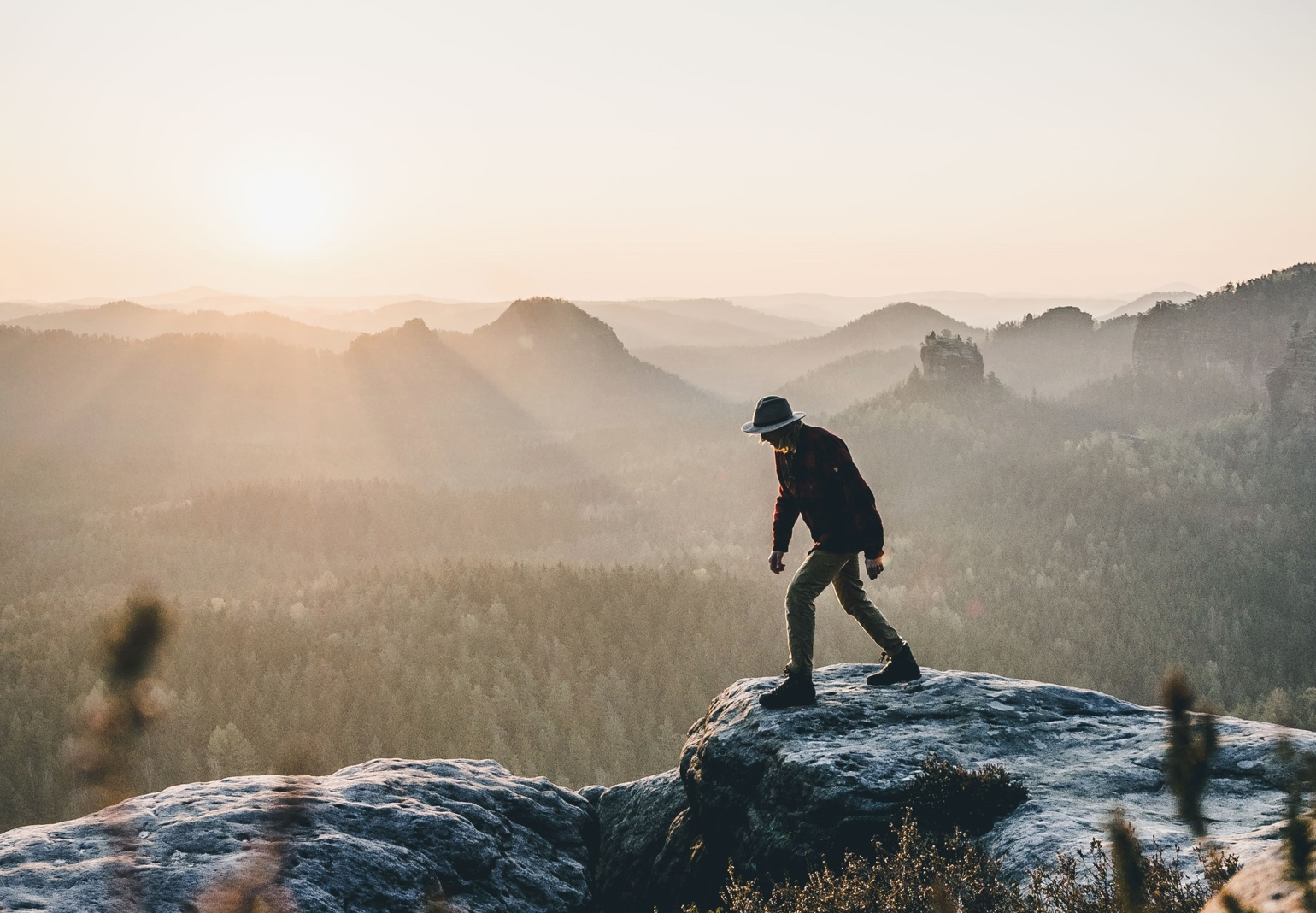 A person walking on a rock during sunrise.