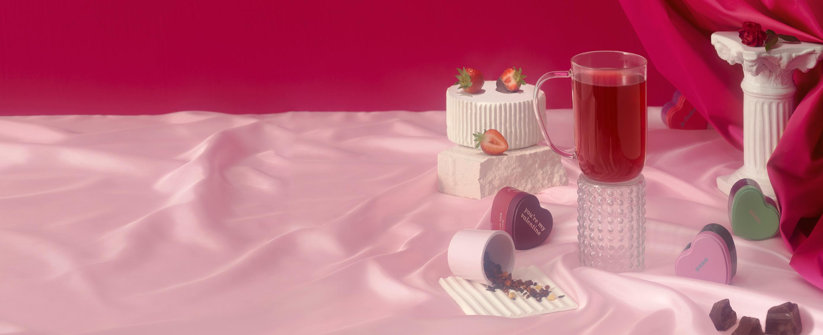 Une tasse Nordic remplie de thé et entourée de fraises et de boîtes en forme de cœur.