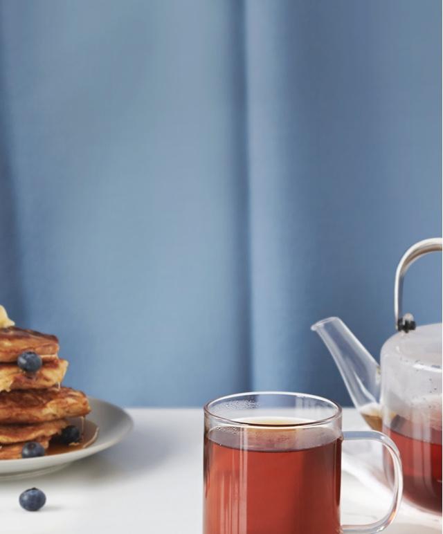 Pile de pancakes aux bleuets avec sirop d'érable, tasse 16 oz en verre transparent remplie de thé noir de qualité supérieure.