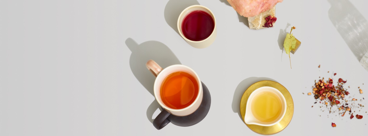 3 ceramic mugs filled with hot wellness teas featuring all-natural mood-boosting ingredients.