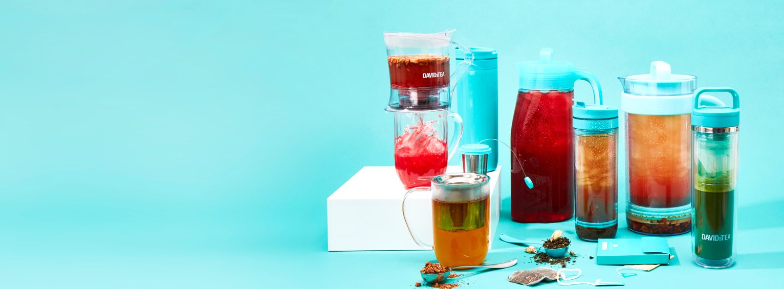 Teal 2 L pitchers of iced tea, teal 16 oz tea travel mugs, clear 16 oz mug with iced tea and stainless steel tea infusers.