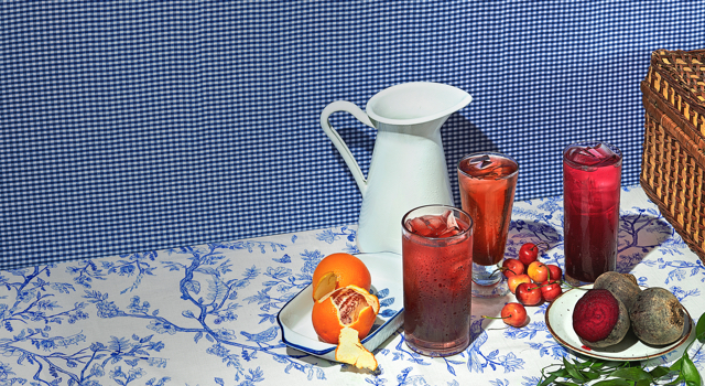 Three glasses grouped together filled with fruity iced teas surrounded by fresh fruits and a picnic basket.