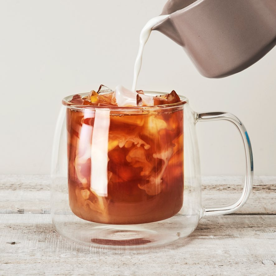 Milk pouring into clear 18 oz double-walled glass latte mug filled with ice and premium black tea.